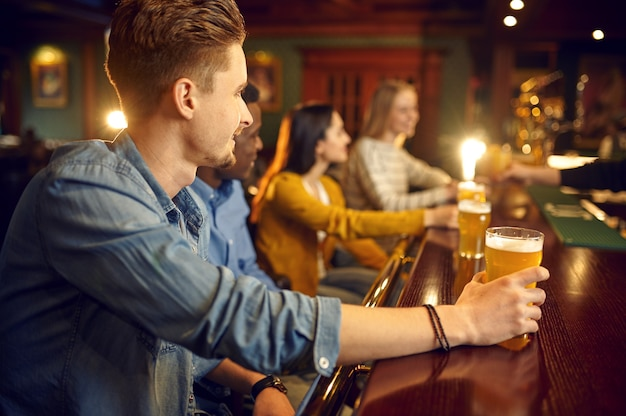 Fröhliche freunde trinken bier an der theke in der bar