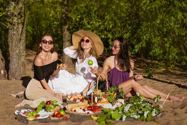 Fröhliche freundinnen amüsieren sich im sommer bei einem picknick fröhlicher gesellschaft schöner mädchen, junger kaukasier...