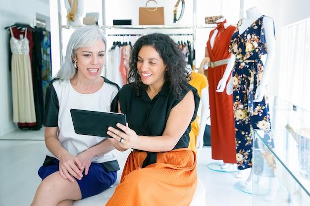 Fröhliche freundinnen, die zusammen sitzen und tablette benutzen, kleidung und einkäufe im modegeschäft besprechen. speicherplatz kopieren. konsum- oder einkaufskonzept