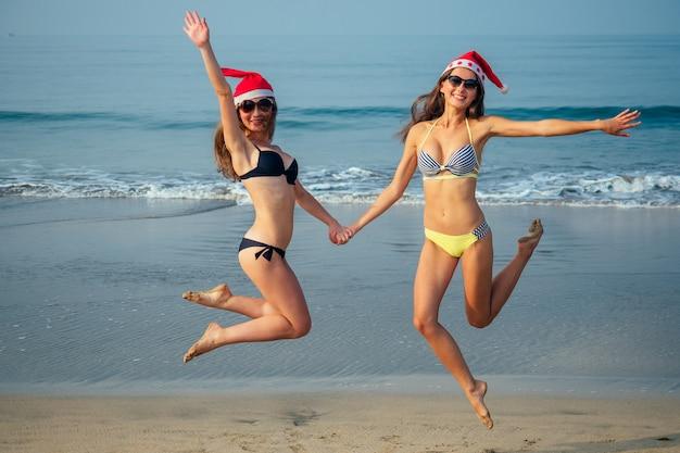 Fröhliche freundinnen in einer weihnachtsmütze und einem bikini, die auf den strand springen.