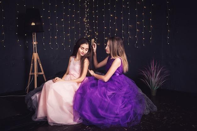 Fröhliche freundinnen. zwei mädchen kämmen sich gegenseitig die haare und sitzen nebeneinander im studio auf dunklem hintergrund. speicherplatz kopieren. Premium Fotos