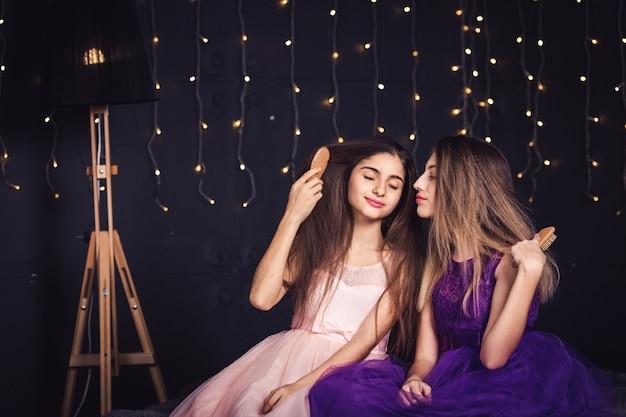 Fröhliche freundinnen zwei mädchen kämmen sich gegenseitig die haare und sitzen nebeneinander