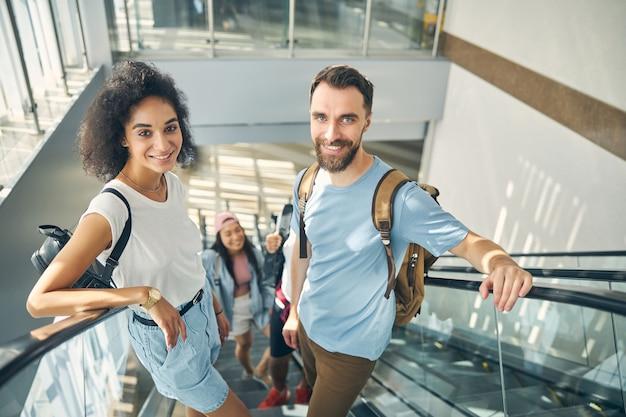 Fröhliche freundliche menschen, die mit gepäck reisen, steigen auf die rolltreppe zum abflugbereich am flughafen