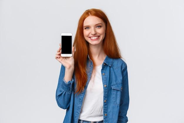 Fröhliche freundliche rothaarige frau, die wasser-app prüft, bleiben mit smartphone-anwendung hydratisiert