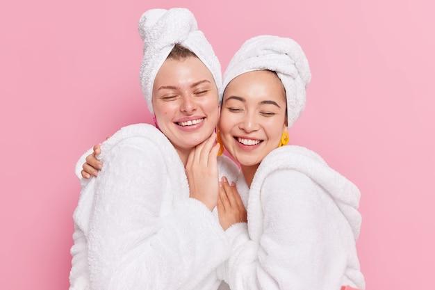 Fröhliche, freundliche, vielfältige frauen mit gesunder, sauberer haut umarmen und lächeln aufrichtig, halten die augen geschlossen, tragen weiße bademäntel und handtücher über dem kopf, nachdem sie einzeln auf rosafarbenem hintergrund geduscht haben