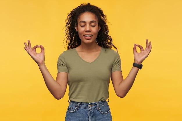 Fröhliche friedliche junge frau mit geschlossenen augen in freizeitkleidung meditiert und praktiziert yoga isoliert über gelber wand