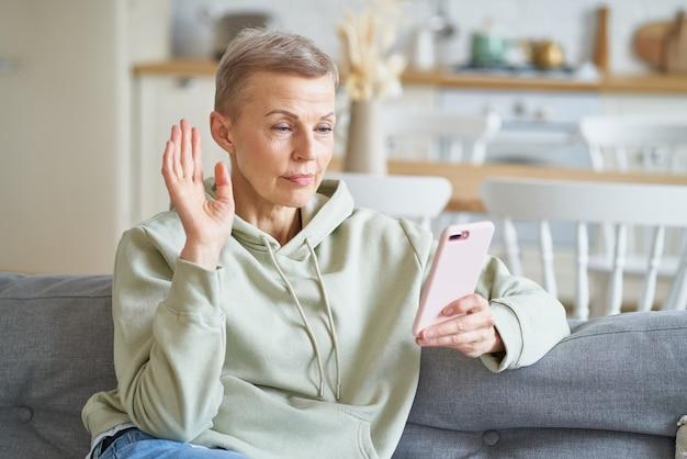Fröhliche, fröhliche ältere frau, die einen videoanruf mit freund oder familie auf dem smartphone hat, während sie darauf sitzt