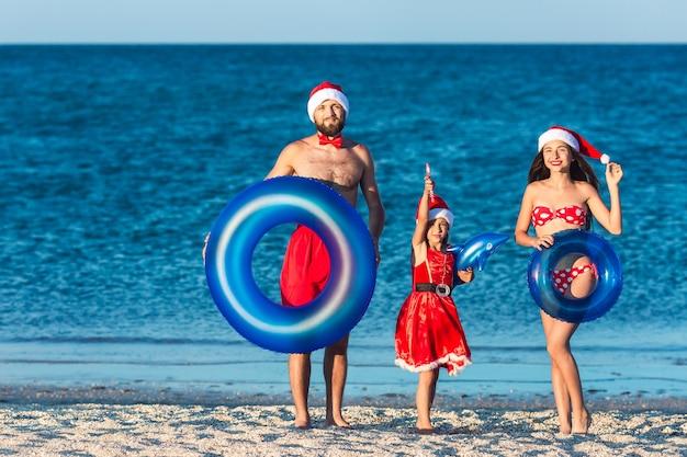 Fröhliche fröhliche familie, gekleidet in weihnachtsmützen und mit aufblasbaren kreisen, feiert sommerweihnachten am meeresstrand.