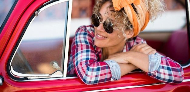 Fröhliche, fröhliche junge erwachsene frau lächelt und genießt es, in ihrem roten trendigen auto zu sitzen und zu starten und für eine reise oder einen urlaub zu fahren, der einen freudigen lebensstil weiblicher menschen unabhängig macht