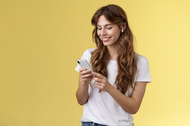 Fröhliche fürsorgliche zarte weibliche freundin lockiges langes haar halten smartphone-picking-lied hören weg nach hause...