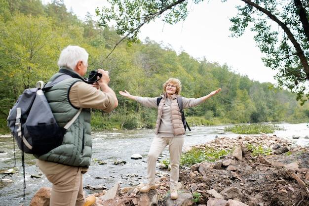 Fröhliche gealterte aktive frau mit ausgestreckten armen, die ihren ehemann mit kamera betrachten, während beide am fluss stehen