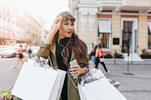 Fröhliche gebräunte frau, die sonnenbrille hält, während sie nach dem einkaufen nach hause geht