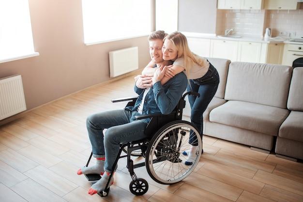 Fröhliche gefühle. junger mann mit behinderung, der auf rollstuhl sitzt. frau steht hinter ihm und umarmt ihn. schönes paar verbringen zeit zusammen.