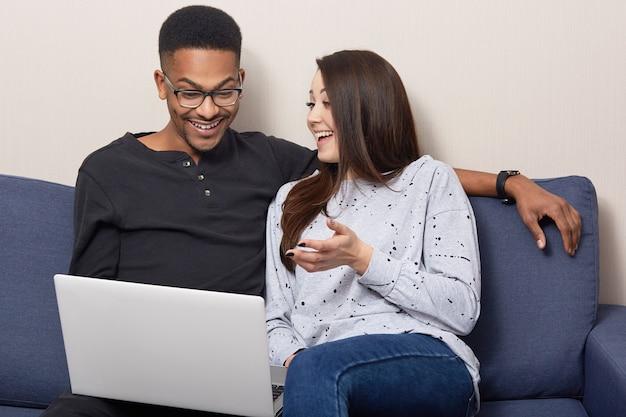 Fröhliche gemischte rassenpaare verwenden laptop-computer zum ansehen von filmen, sitzen zusammen auf dem sofa über wohnraum, durchsuchen informationen