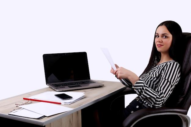 Fröhliche geschäftsdame, die an der kamera an ihrem arbeitsplatz lächelt