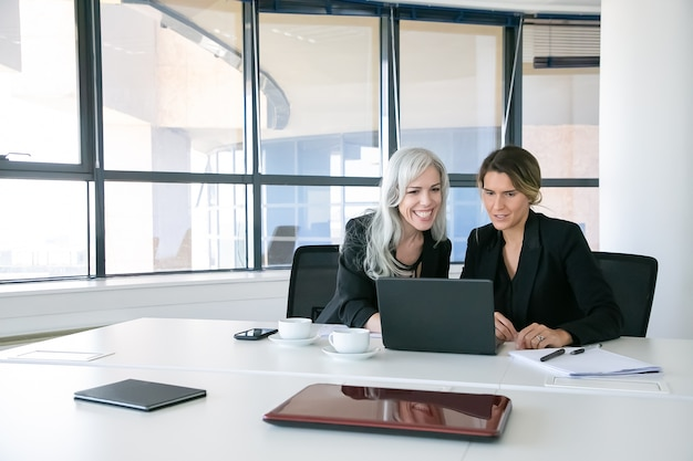 Fröhliche geschäftsdamen, die laptopanzeige betrachten, sprechen und lächeln, während sie am tisch mit tassen kaffee im büro sitzen. teamwork und kommunikationskonzept