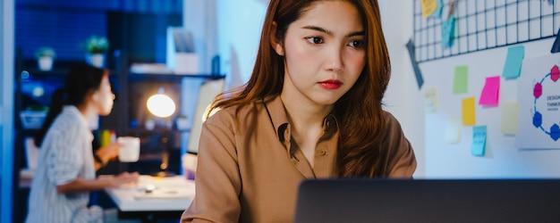 Fröhliche geschäftsfrau aus asien, die sich in einer neuen normalen situation zur virenprävention sozial distanziert, während sie in der büronacht bei der arbeit mit laptop-online-geschäft überstunden macht.