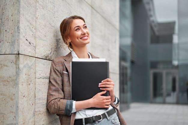 Fröhliche geschäftsfrau, die sich an das büro lehnt, dokumente hält, pause im freien genießt