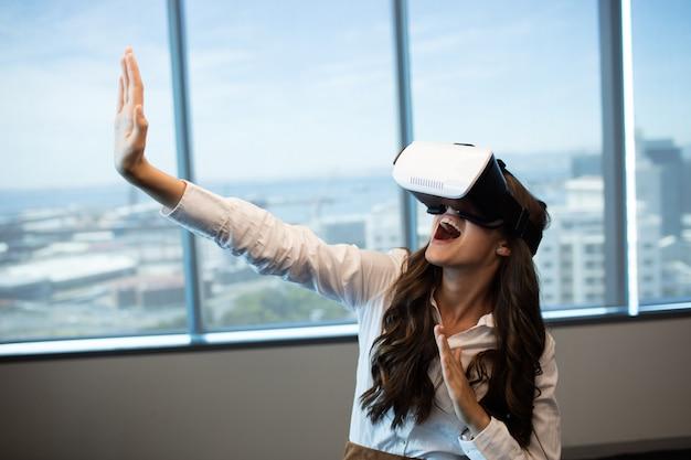 Fröhliche geschäftsfrau gestikuliert mit virtual-reality-brille