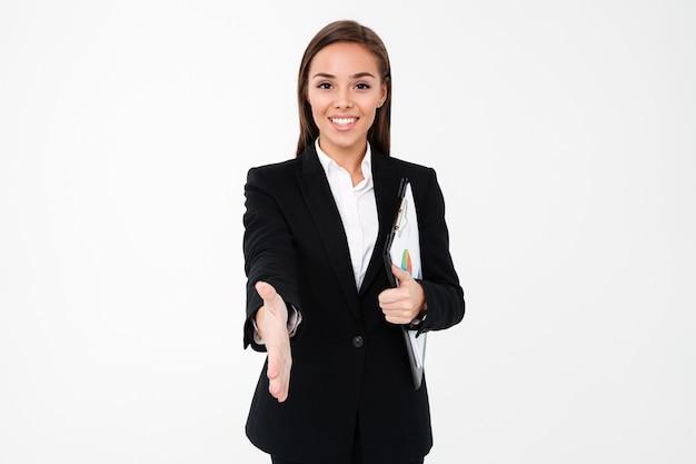 Fröhliche geschäftsfrau hält dokumente und gibt ihnen eine hand.