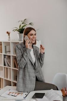 Fröhliche geschäftsfrau lächelt, während sie per telefon kommuniziert. frau in der grauen karierten jacke, die im weißen büro aufwirft.