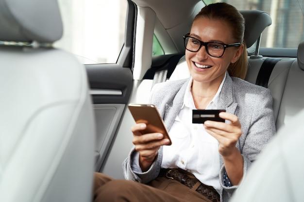 Fröhliche geschäftsfrau mit brille, die ihr smartphone und ihre kreditkarte benutzt, um etwas zu kaufen
