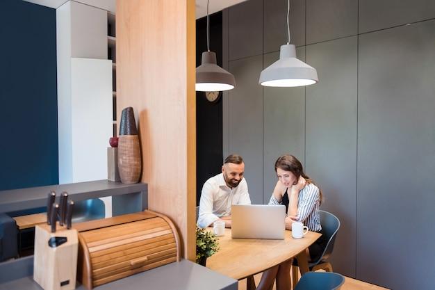 Fröhliche geschäftspartner in stilvollem outfit sitzen zusammen am tisch und schauen auf den computerbildschirm computer