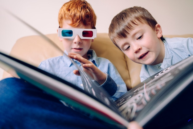 Fröhliche geschwister, die ein buch zusammen mit 3d-brille lesen. lehrbücher und lernaktivitäten für intellektuell aktive kinder, die zu hause freizeitaktivitäten teilen.