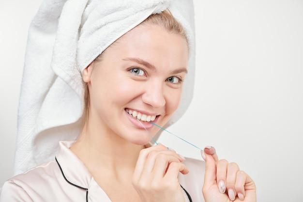Fröhliche gesunde junge frau mit zahnigem lächeln unter verwendung von zahnseide