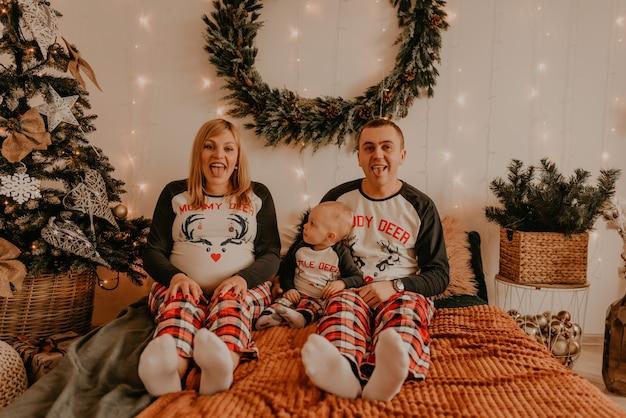 Fröhliche glückliche familie im schlafanzug mit kind, das auf bett im schlafzimmer sitzt. eltern zeigen zungen. neujahr familienkleidung sieht outfits. valentinstag feier geschenke