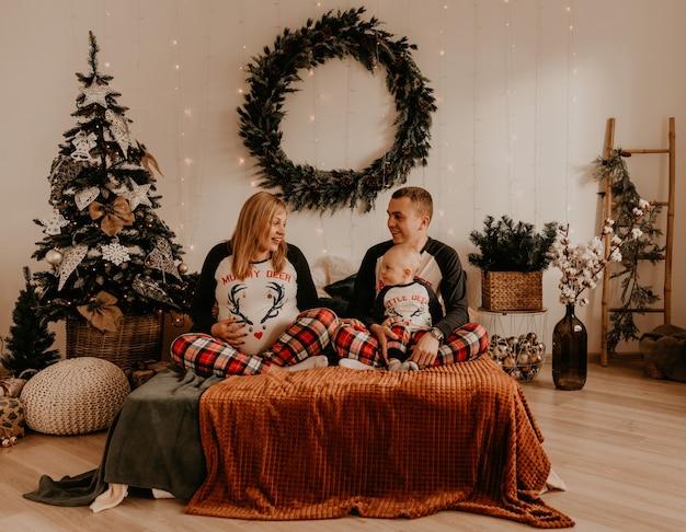 Fröhliche glückliche familie im schlafanzug mit kind liegen auf dem bett im schlafzimmer. neujahr familienkleidung sieht outfits. valentinstag feier geschenke