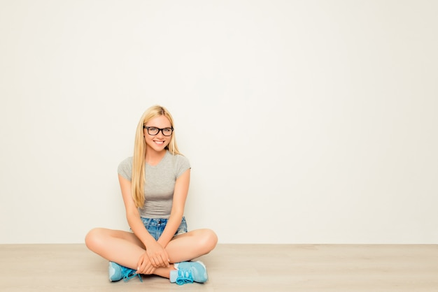Fröhliche glückliche frau in den gläsern, die auf boden mit gekreuzten beinen sitzen