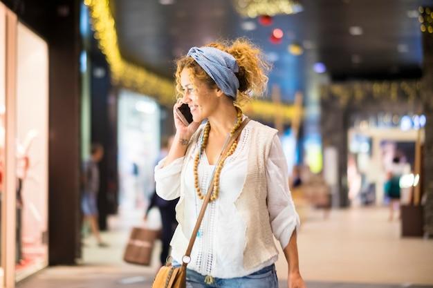 Fröhliche, glückliche frau kauft im einkaufszentrum ein, während sie mit dem telefon telefoniert und sich die geschäfte ansieht, um zu entscheiden, was sie kaufen und tragen soll, um mode und schöne städtische moderne dame zu sein