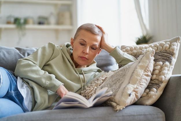 Fröhliche glückliche frau liest buch und lächelt beim entspannen auf dem sofa zu hause