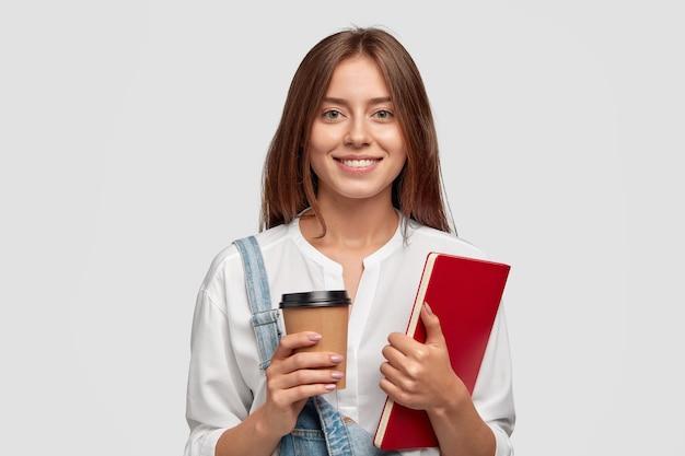Fröhliche glückliche frau mit zahnigem lächeln, kaffee zum mitnehmen und rotes buch, froh, das studium zu beenden