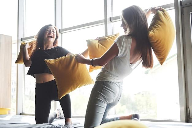 Fröhliche glückliche freundinnen kämpfen mit kissen.
