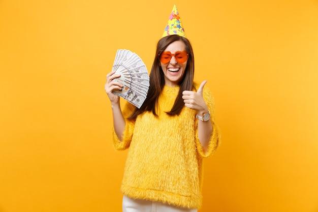Fröhliche, glückliche junge frau in orangefarbenem herzbrillen-geburtstagshut, der den daumen zeigt, der bündel viele dollar-bargeld hält und isoliert auf gelbem hintergrund feiert. menschen aufrichtige emotionen, lebensstil.