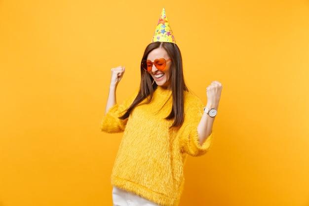 Fröhliche, glückliche junge frau in orangefarbener herzbrille, geburtstagsparty, die fäuste ballt, wie sieger, die den urlaub genießen, einzeln auf hellgelbem hintergrund feiern. menschen aufrichtige emotionen, lebensstil.