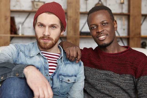 Fröhliche glückliche junge kaukasische und afrikanische freunde, die stilvolle kleidung im gespräch tragen