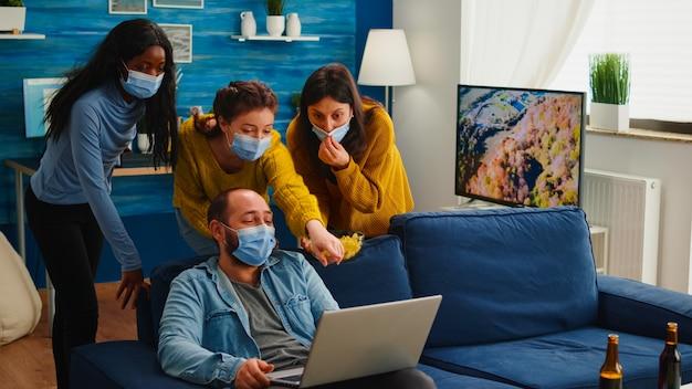 Fröhliche, glückliche, multiethnische freunde, die sich ein foto auf dem laptop ansehen und gemeinsam spaß haben, soziale distanz mit gesichtsmaske zu halten, die die ausbreitung von coronaviren verhindert. diverse leute, die eine neue normale party genießen