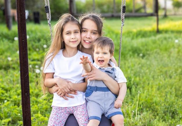 Fröhliche glückliche zwei schwestern und ein kleinkindbruder in leichter frühlingskleidung. viel spaß beim fahren auf einer roten straßenschaukel in einem blühenden grünen hausgarten und lachen sie in einem breiten lächeln