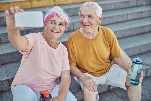Fröhliche grauhaarige kaukasische dame, die ein foto von sich und ihrem ehepartner auf der treppe macht