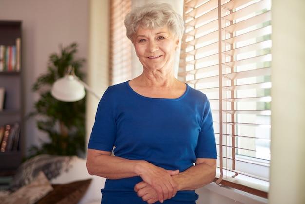 Fröhliche großmutter, die neben dem fenster steht