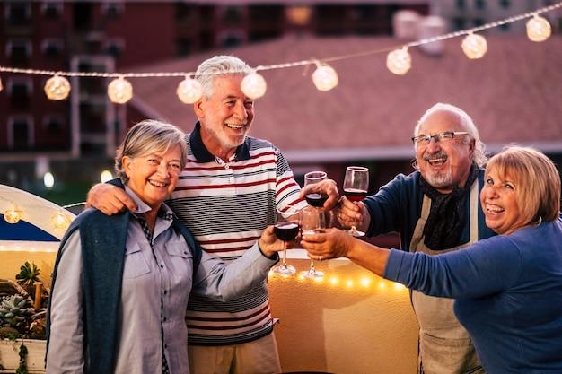 Fröhliche gruppe alter kaukasischer seniorenfreunde feiern nachts zusammen, klirren und rösten mit rotwein - beenden sie den coronavirus-notfall und die menschen in freundschaft wieder frei