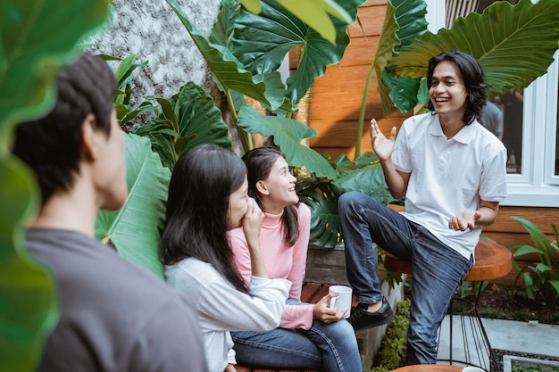 Fröhliche gruppe von freunden beim sitzen und plaudern auf einem hinterhof