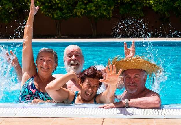 Fröhliche gruppe von freunden, die das schwimmbad zusammen mit sonnenlicht und transparentem wasser genießen