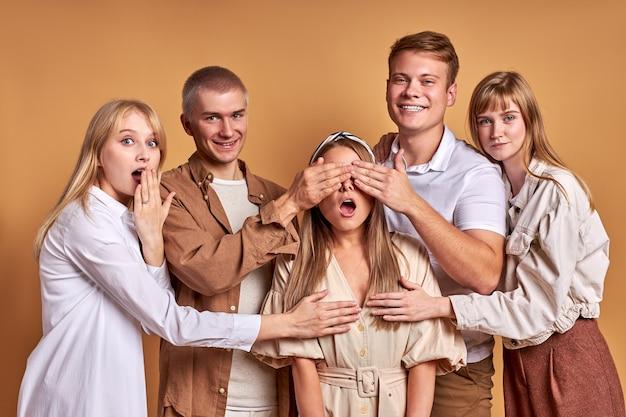Fröhliche gruppe von jugendlichen, die die brust ihrer freundin schließen und spaß haben und überrascht sind