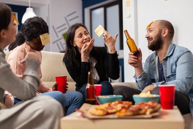 Fröhliche gruppe von kollegen, die nach der arbeit im büro ein spiel von scharaden genießen. multiethnische menschen spielen ein nachahmungskonzept für unterhaltsame aktivitäten, während sie pizza essen und bier trinken