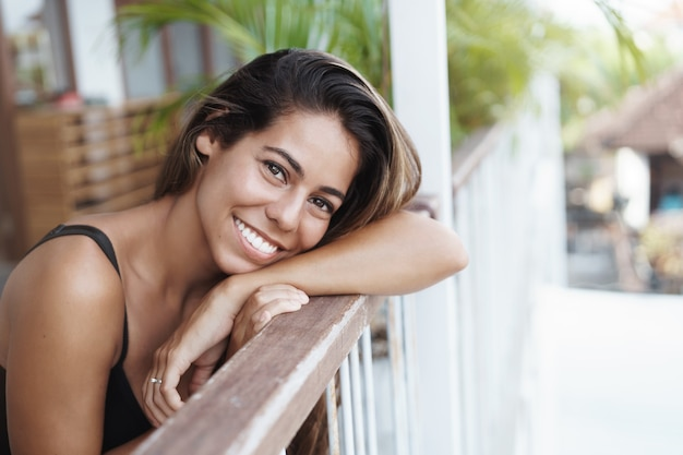 Fröhliche, gut aussehende, junge, gebräunte frau lehnt sich an die terrassenschiene und schaut glücklich