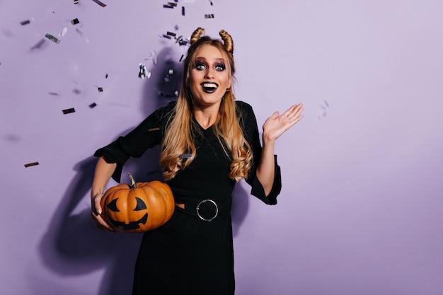 Fröhliche, gut gekleidete hexe mit halloween-kürbis. emotionaler blonder vampir, der spaß an der party hat.